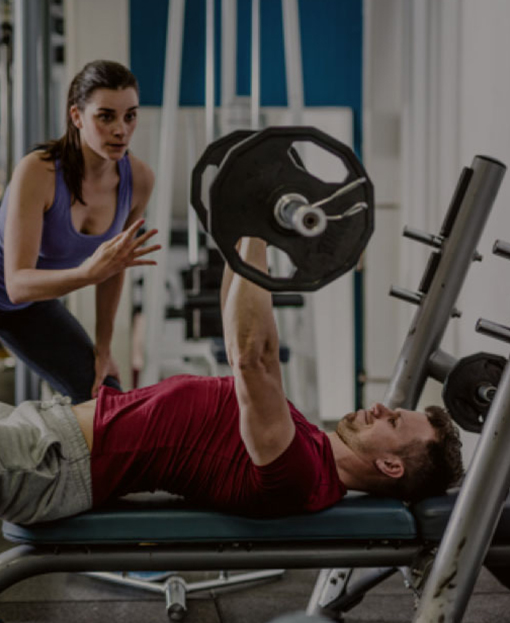 Trainer coaching man on weight lifting workout.
